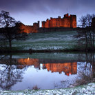 Picture - Alnwick Castle reflected in the water in the late afternoon.
