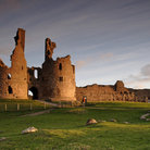 Picture - The ruins of Dunstanburgh Castle at sunset in Alnwick.