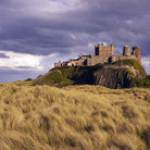 Picture - Grass field in front of Bamburgh Castle.