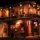 Picture - A brick building lit up at night on Bourbon Street in New Orleans.