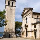 Picture - A clock tower stands in front of the Cathedral of the Assumption of the Blessed Virgin Mary in Pula.