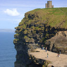 Picture - Four story tower on top shows scale of the cliffs of Moher.