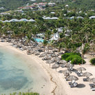 Picture - View over Grand Cul de Sac Beach with beach umbrellas and chairs lining the ocean front.