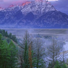 Picture - Sunrise over water and mountains in Grand Teton National Park.
