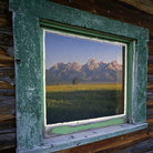Picture - Window of a ranch house with the reflection of the Teton Mountain Range, located in Grand Teton National Park.