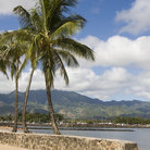 Picture - The seawall at Haleiwa with mountains in the background.