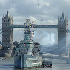 Picture - The H.M.S Belfast firing guns in London with the Tower Bridge in behind.
