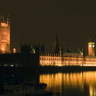 Picture - Houses of Parliament reflecting on the water at night in London.