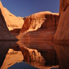 Picture - The calm waters of Lake Powell reflect the surrounding rock.