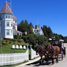 Picture - Horse drawn carriage in front of a cottage on Mackinac Island.