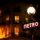 Picture - Sign for the Paris Metro at night.
