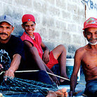 Picture - Fishermen work on nets in town of Santa Fe.