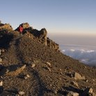 Picture - A hiker on the summit of Mount Meru.