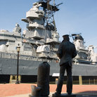 Picture - Sailor statue with the vintage WWII USS Wisconsin battleship in background.