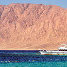Picture - Boats and a dramatic cliff wall of off the town of Nuweiba.