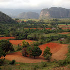 Picture - Red fields and the dramatic cliffs of Parque Nacional Vinales.
