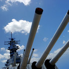 Picture - Guns on the deck of the USS Missouri with USS Arizona Memorial in the distance at Pearl Harbor.