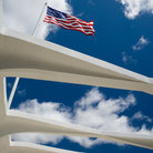 Picture - US flag flies over the USS Arizona Memorial in Pearl Harbor.