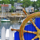 Picture - Boat wheel with boats in the background in Rockport, MA.