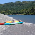 Picture - Kayaks on the shore of the Rogue River.