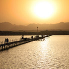 Picture - People walking along a bridge with the sun setting over the Sinai Mountains in Sharm El Sheikh.