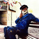 Picture - A life-like statue of a sailor sits on a bench outside of the Key West Shipwreck Historeum.