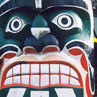 Picture - Close up of a carved face on a totem pole in Stanley Park in Vancouver.