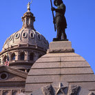 Picture - Statue remembering the Alamo with the Texas State Capitol Building in the background, Austin, Texas.