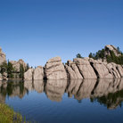 Picture - A calm day at Sylvan Lake, with surrounding rocks.