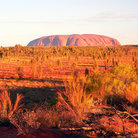 Picture - Ayers Rock and the desert floor.