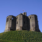 Picture - Warkworth Castle on grassy hill above River Coquet.
