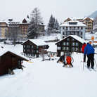 Picture - Holiday makers ski and sled in the village of Wengen.