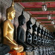 A holy statue of buddha between line of statues in black at Wat Suthad, Bangkok.