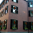 Brick apartment with windows adorned in Christmas wreaths in Boston, MA.