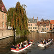 Canal boats full of tourists in Bruges.