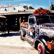 An old truck is displayed in front of a gift shop in Key West.