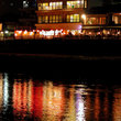A riverside restaurant in Kyoto at night.
