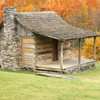 Log cabin surrounded by Fall colors in Grayson Highlands State Park, Virginia.