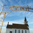 Metal archway over entrance to small church cemetery in North Dakota.