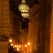 "The dome of the Pantheon over ""Rue de Bievres"" at night in Paris."