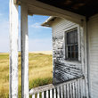 Porch of weathered building on North Dakota grassland.