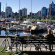 Park bench and boats in front of the Vancouver skyline.