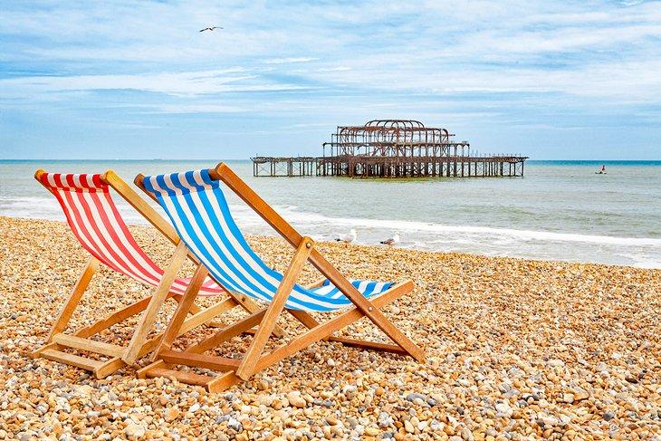 Sillas de playa en Brighton Beach con West Pier en el fondo