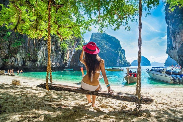 Турист, наслаждающийся пляжными качелями на острове Лао Лэдинг, Краби.