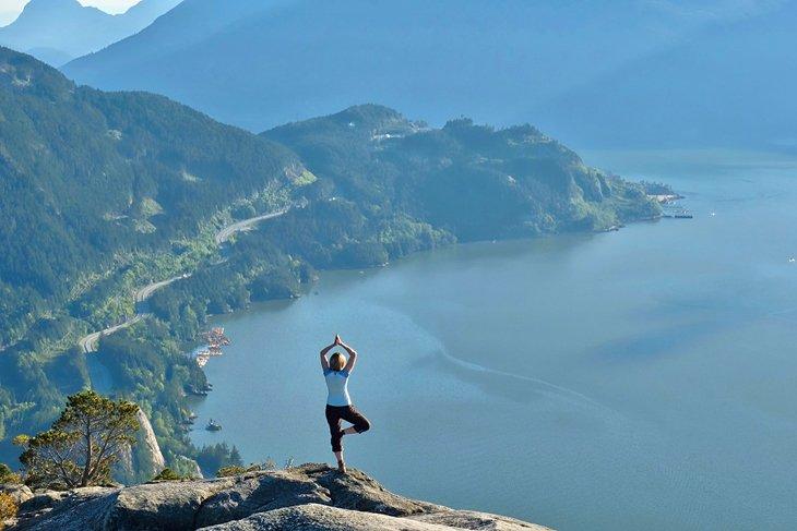 Caminante haciendo yoga en la cima del Jefe