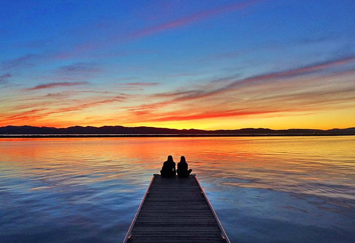 A couple enjoying sunset on Lake Champlain