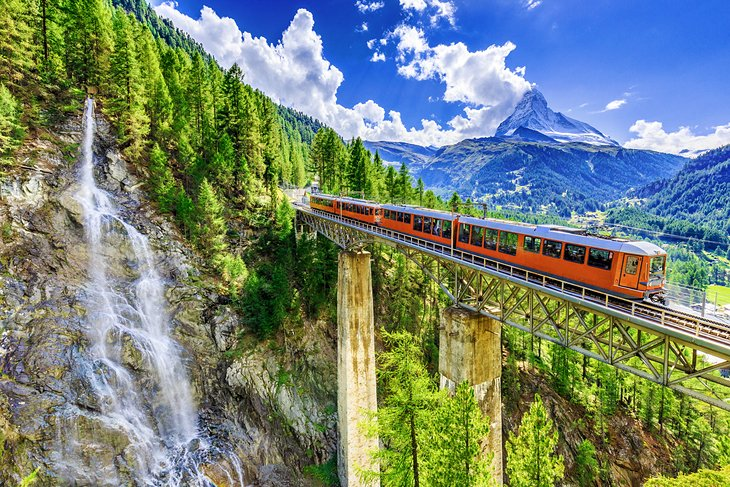 Train crossing a bridge in Switzerland with the Matterhorn in the distance