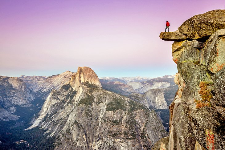 Hiker standing on Glacier Point overlooking Half Dome in Yosemite National Park