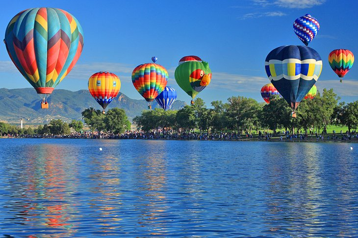 Hot air balloons launching over a lake in Colorado Springs