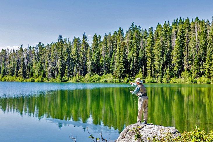 Pescador con mosca probando suerte en Jenny Lake, Parque Nacional Grand Teton